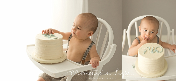 Boy eating frosting off first birthday cake in baby photography studio in Montgomery, Texas