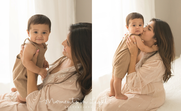 baby boy with mom wearing light colors on bed in Houston photo studio