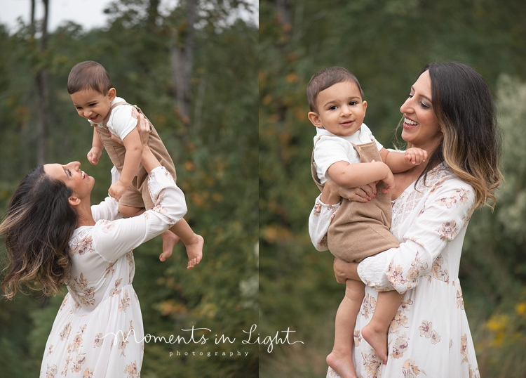 Woman in white floral dress smiling and holding up baby boy by Houston family photographer