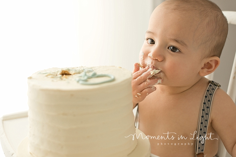 Baby boy eating cake in Houston baby photography studio