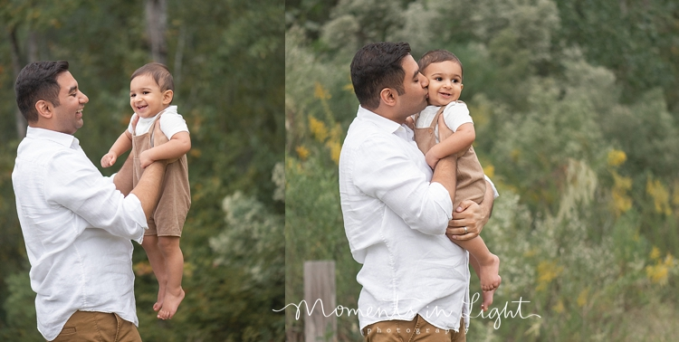 Father holding and kissing baby boy  in a field in The Woodlands