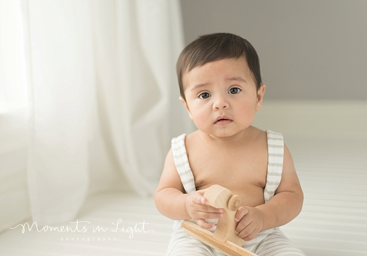 six month old baby boy in white overalls in Houston photo studio