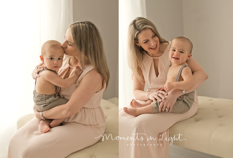 Mother holding baby boy on lap in window of baby photography studio in Montgomery, Texas