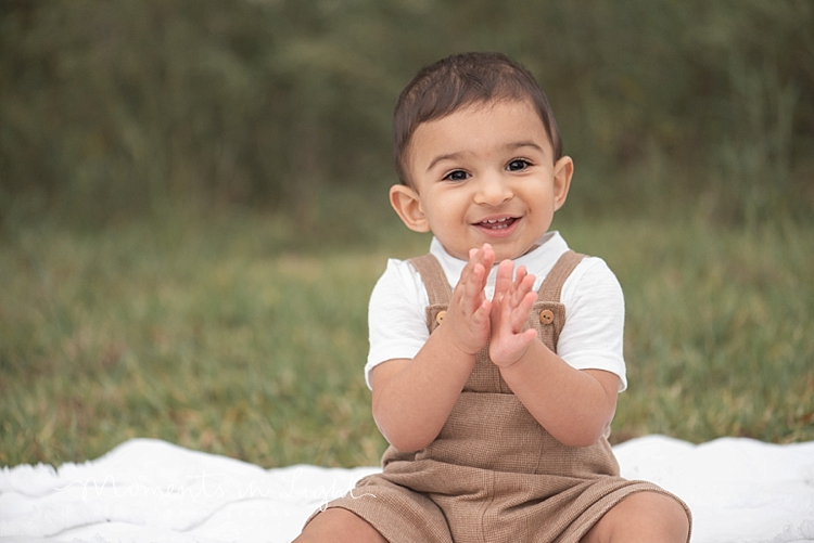 Baby boy wearing brown overalls clapping in a field by family photographer in Montgomery, Texas