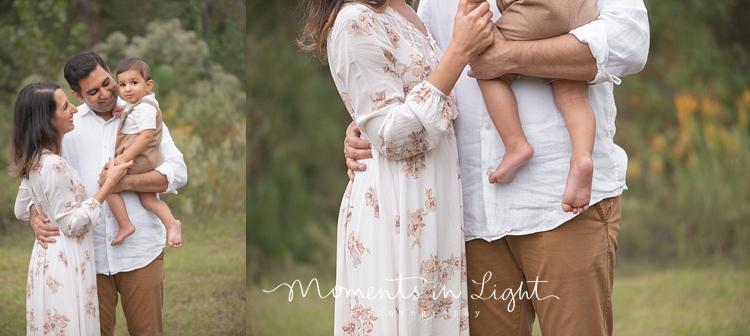 Mother and father holding baby boy in a field by Houston family photographer