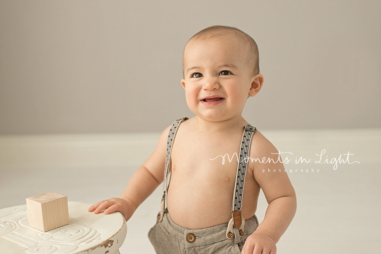 Young boy in suspenders playing with wooden block in Houston baby photography studio