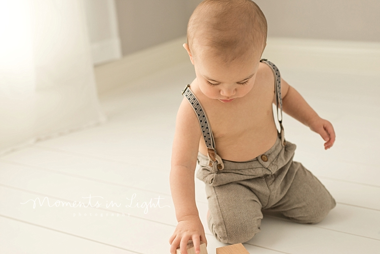 Baby boy in suspenders playing with wooden toys by baby photographer in The Woodlands