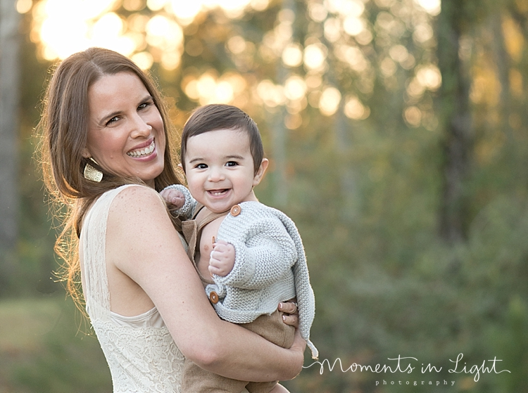 Mother holding baby son in a field by family photographer in The Woodlands