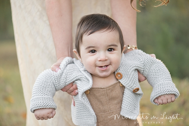 Baby boy in a grey sweater in a field by Montgomery, Texas family photographer