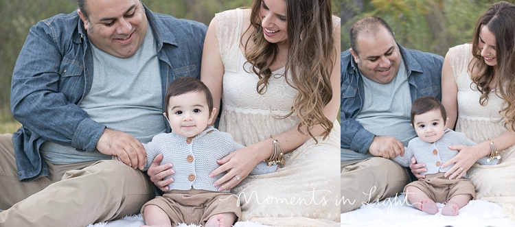 Baby boy sitting on a blanket in a field with parents by Houston family photographer