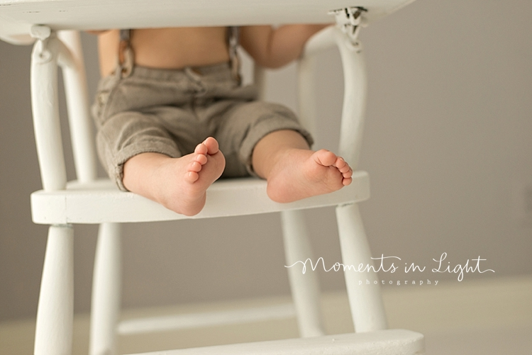 Baby boy's feet hanging off of wooden chair in a baby photography studio in Houston