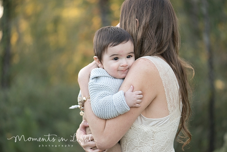 Baby boy looking over his mother's shoulder in a field by Houston family photographer