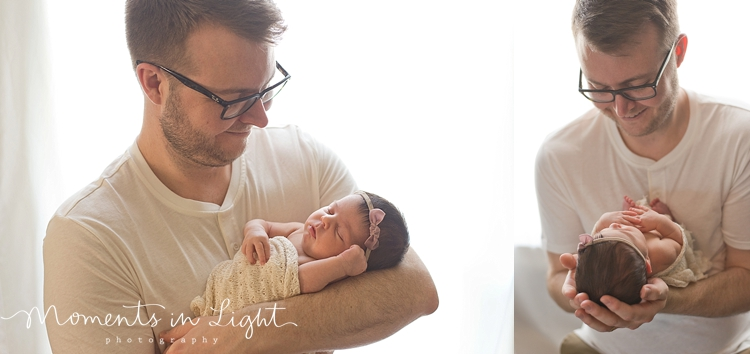 Father smiling down at baby daughter in window of Houston newborn photography studio