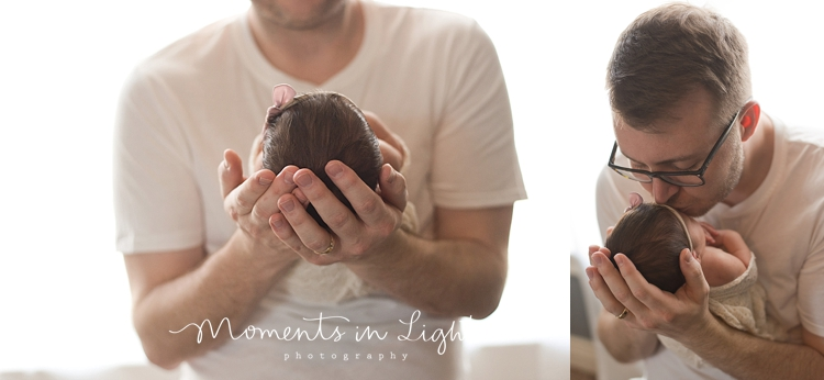 Father kissing baby daughter's head in a newborn photography studio in The Woodlands