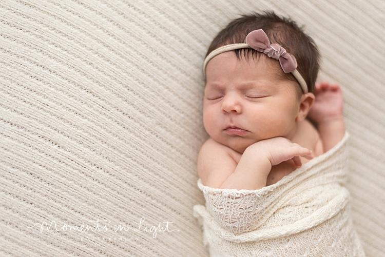 Baby girl wearing pink headband sleeping on bed by Montgomery, Texas newborn photographer