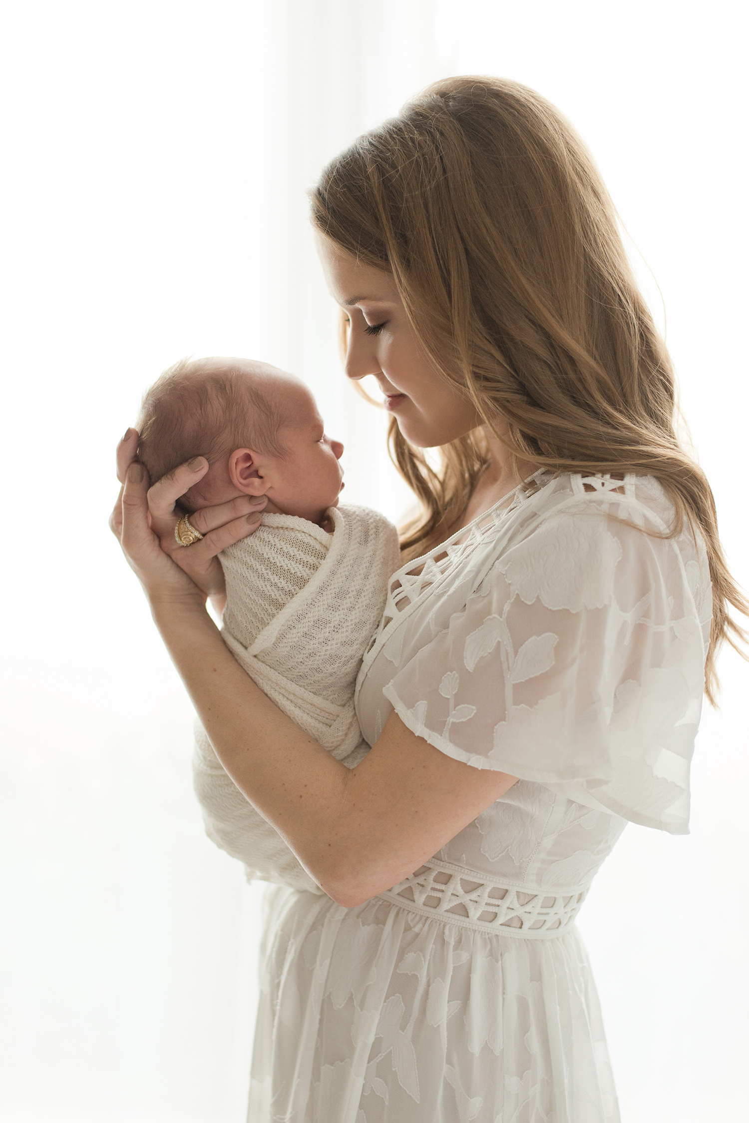 Mom holding newborn baby by window in Montgomery, Texas newborn photo studio